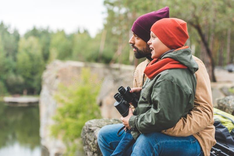 Familj med kikare i skog royaltyfria foton