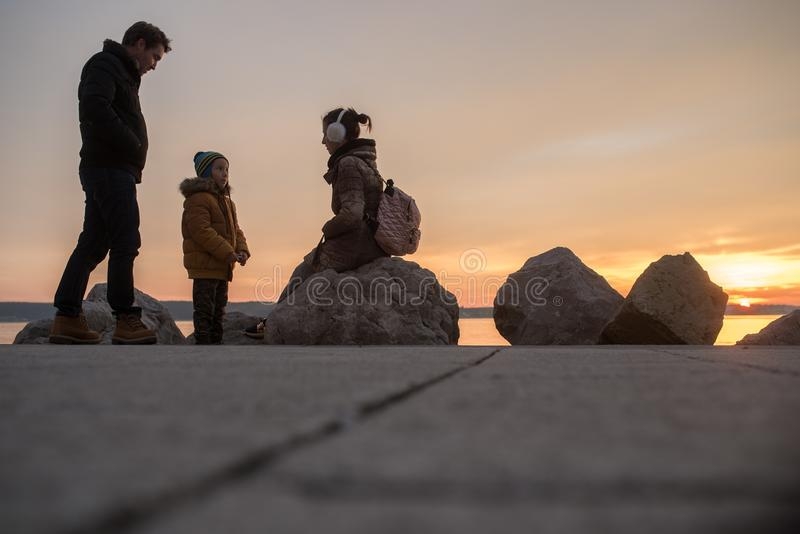 Familj med litet barnpojken på kusten på vintersolnedgången arkivfoto