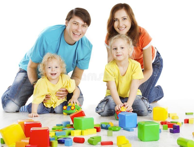Familj med lyckliga ungar som spelar byggnadskvarter, förälderbarn royaltyfri fotografi