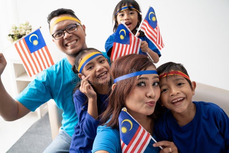 Familj med malaysian flaggatagandeselfie tillsammans royaltyfria foton