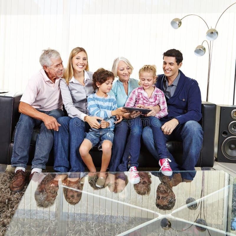 Familj med morföräldrar och minnestavladatoren fotografering för bildbyråer