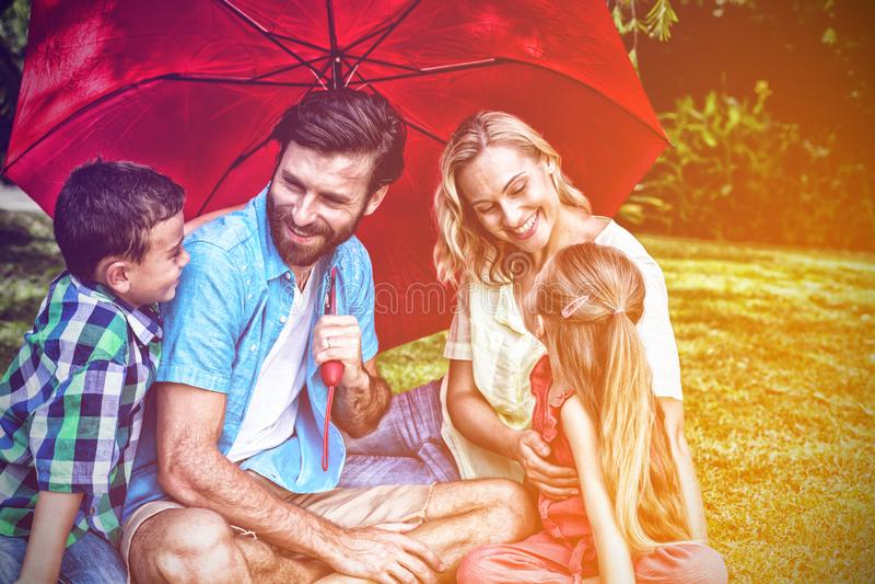 Familj med paraplyet som sitter på gräs på gården arkivfoto