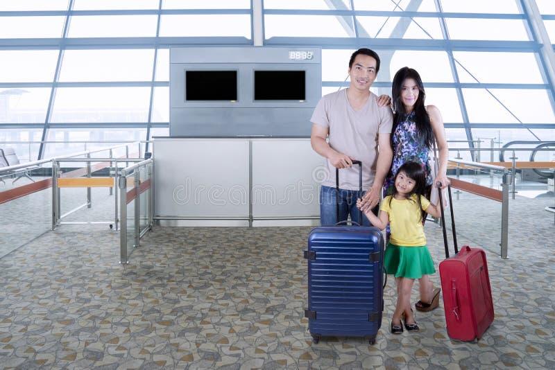 Familj med resväskaanseende i flygplats arkivfoton