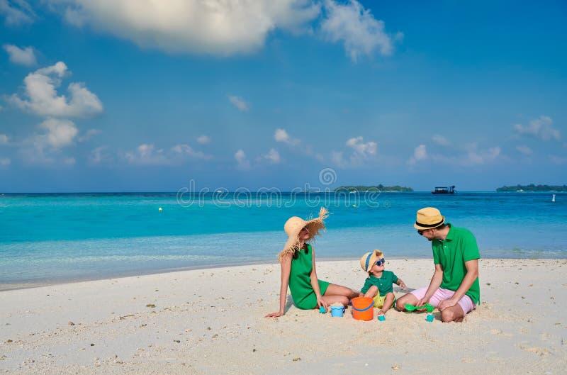 Familj med ?rig pojke tre p? stranden royaltyfri foto