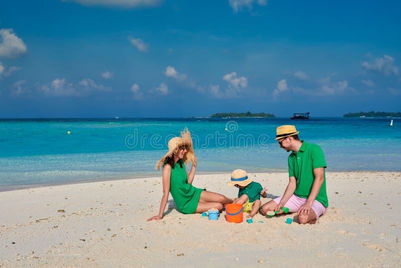 Familj med ?rig pojke tre p? stranden arkivbild