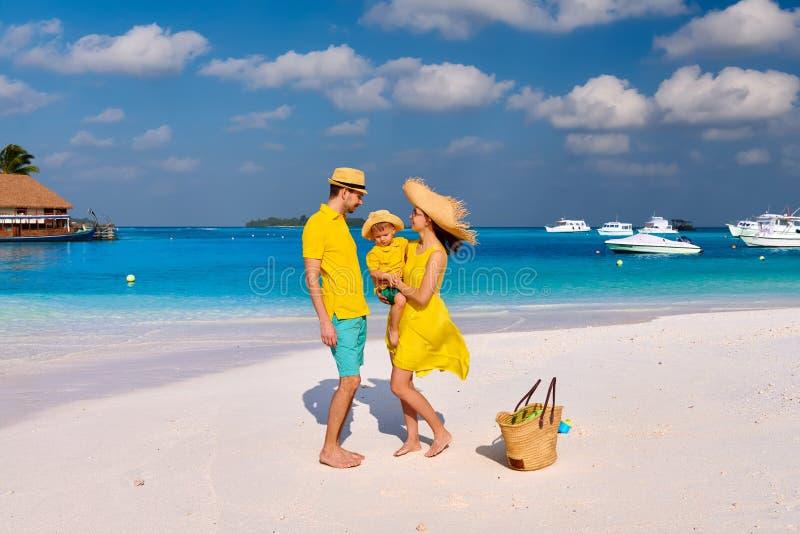 Familj med ?rig pojke tre p? stranden royaltyfria bilder