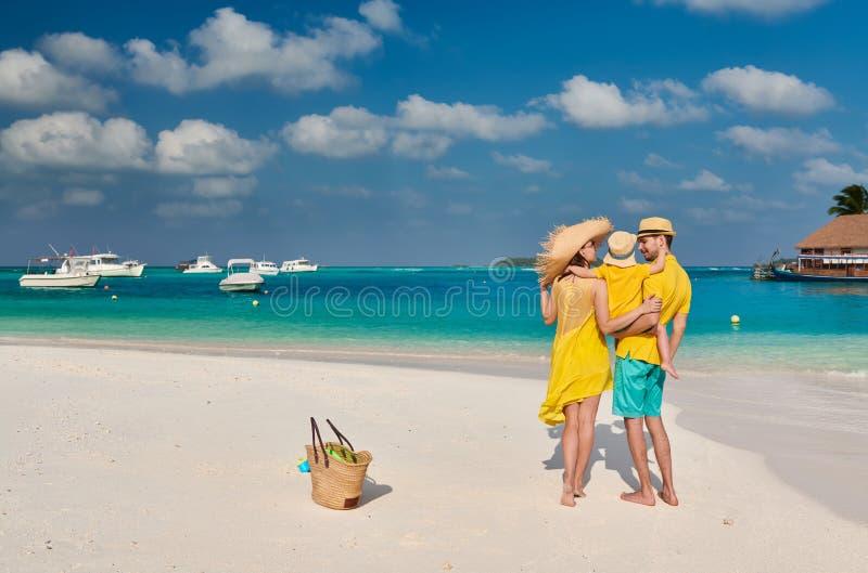 Familj med ?rig pojke tre p? stranden arkivfoto