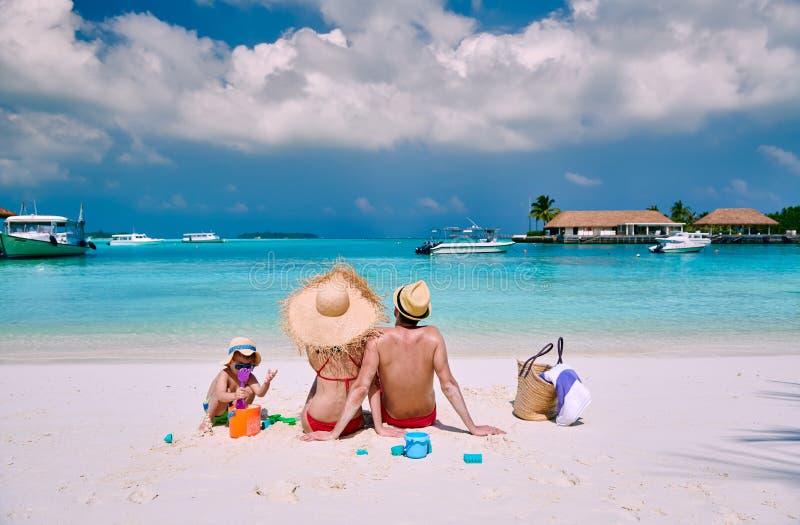 Familj med ?rig pojke tre p? stranden arkivbilder