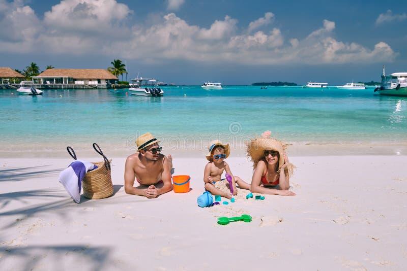 Familj med ?rig pojke tre p? stranden royaltyfri bild