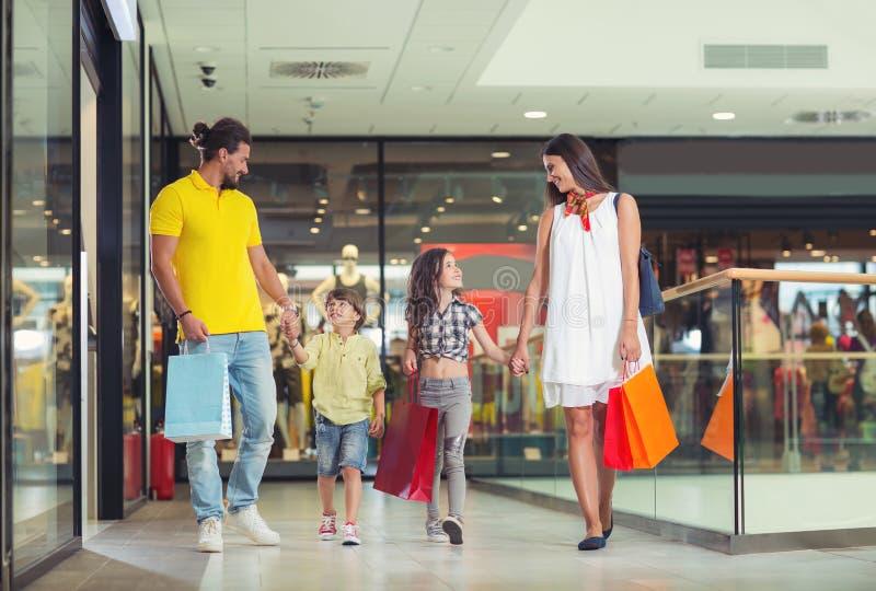 Familj med shoppingpåsar i shoppinggalleria royaltyfri foto