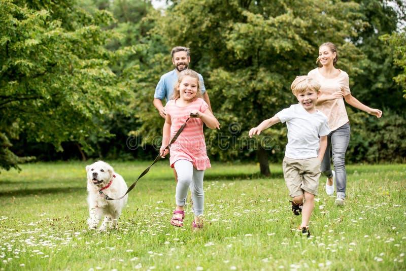 Familj med två barn och hund arkivbild