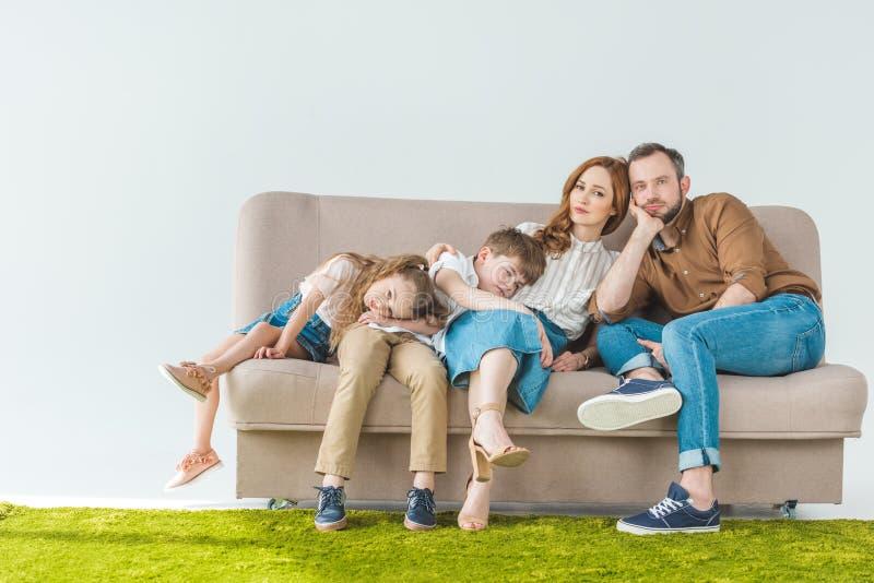 familj med två barn som vilar på soffan och ser kameran royaltyfria bilder