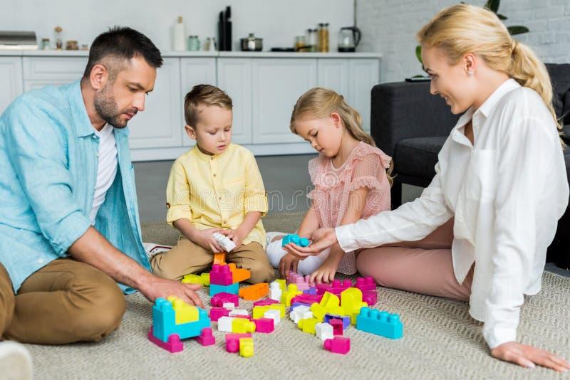 familj med två ungar som sitter på matta och spelar med färgrika kvarter royaltyfria bilder