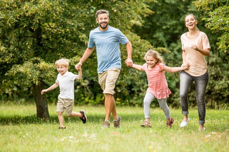 Familj med två ungar tillsammans i sommar royaltyfri fotografi