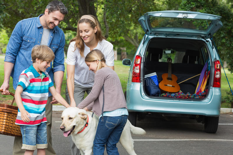 Familj med ungar och den älsklings- hunden på picknicken royaltyfri foto