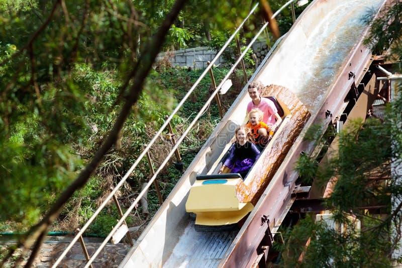 Familj med ungar på berg-och dalbanan i munterhetnöjesfält Barn som rider den snabba dragningen för vattenglidbana i underhållnin royaltyfri fotografi