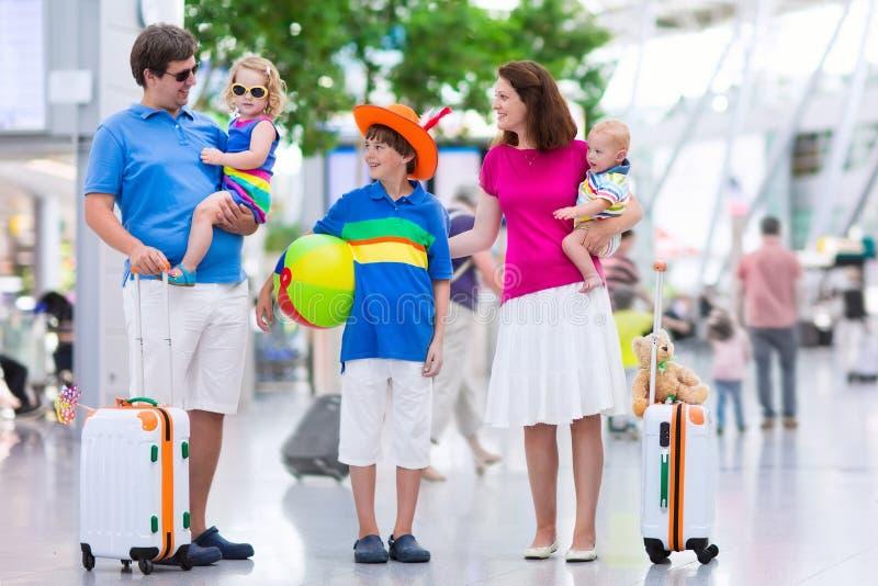 Familj med ungar på flygplatsen arkivbilder