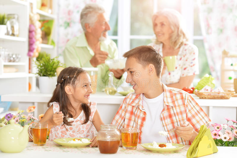 Familj med ungar som har frukosten royaltyfri foto