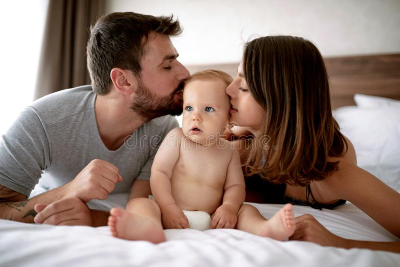 Familj med ungen i morgonen Modern att kyssa för fader behandla som ett barn chil royaltyfri foto