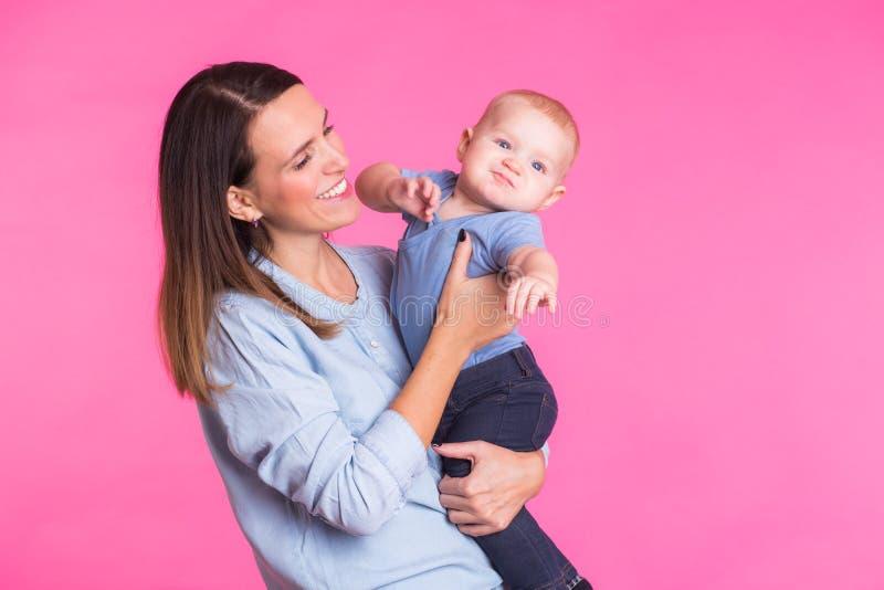 Familj, moderskap, barnuppfostran, folk och barnavårdbegrepp - den lyckliga modern rymmer förtjusande behandla som ett barn över  royaltyfri bild