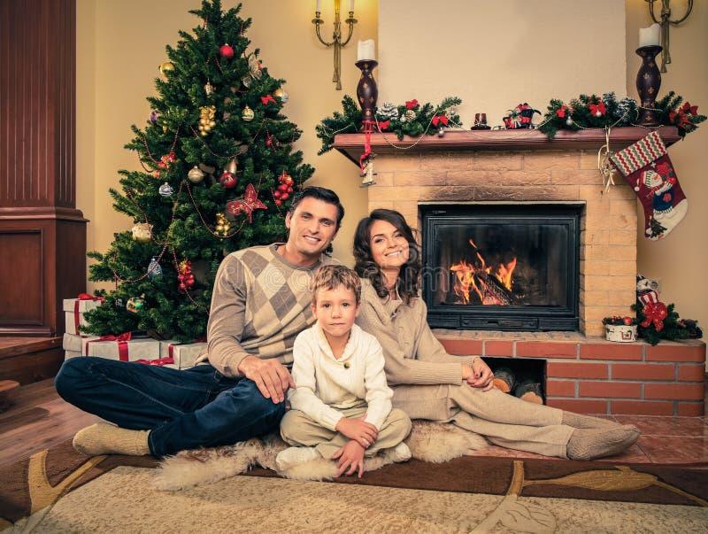 Familj nära spisen i jul dekorerat hus royaltyfria bilder