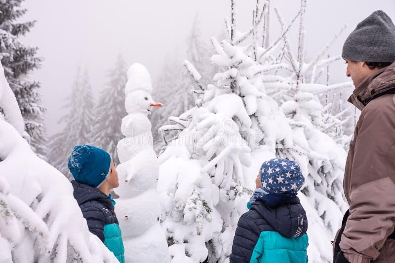 Familj och snögubbe i vintersnöskog arkivbilder
