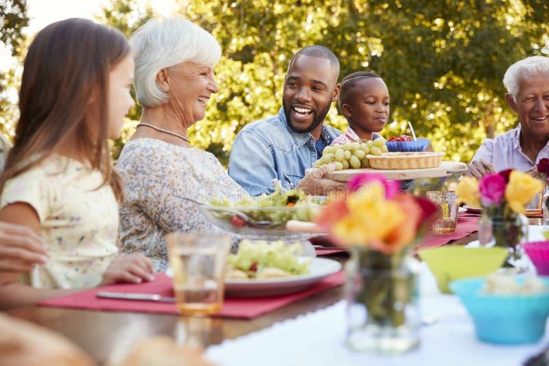 Familj och vänner som talar över lunch på en tabell i trädgård royaltyfri fotografi