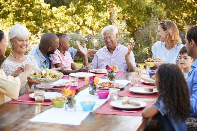 Familj och vänner som talar över lunch på en tabell i trädgård arkivbilder
