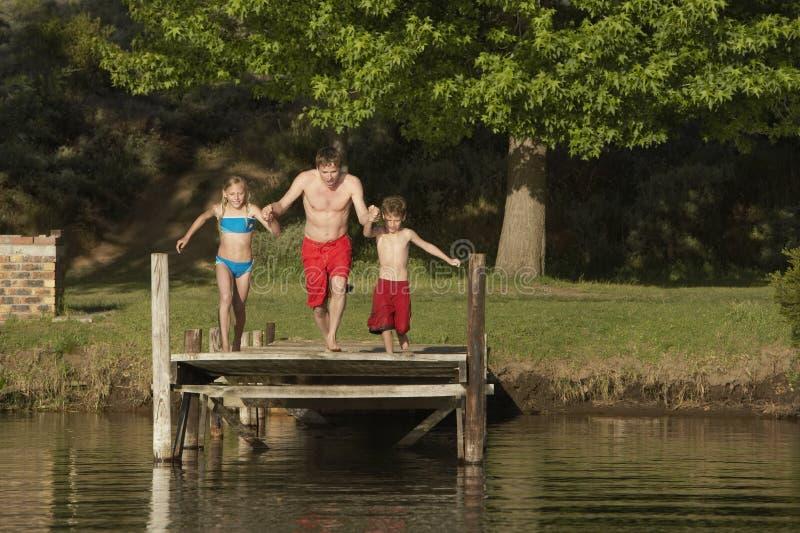 Familj omkring som hoppar i vatten royaltyfri foto