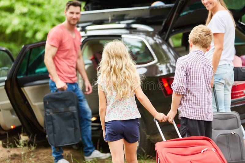 Familj på bilen på resväskapacken arkivbilder