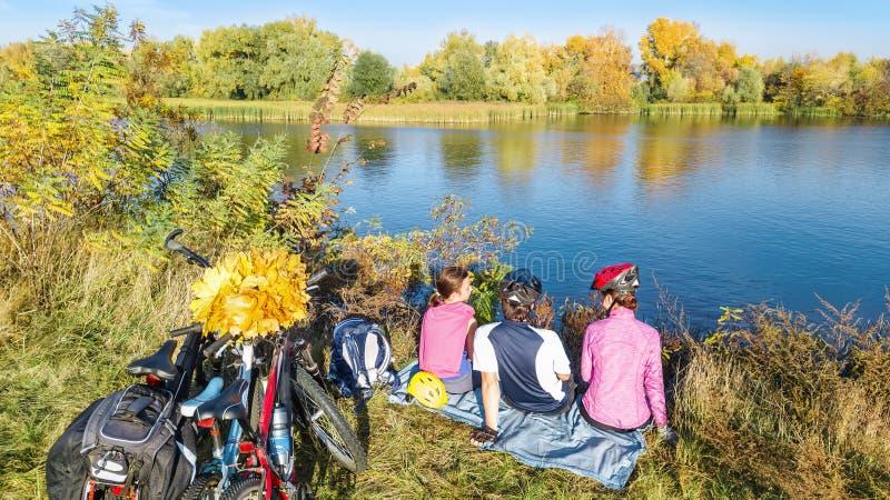 Familj på cykelhöst som utomhus cyklar, aktiv föräldrar och unge på cyklar, flyg- sikt av den lyckliga familjen med att koppla av arkivbild