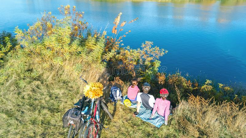 Familj på cykelhöst som utomhus cyklar, aktiv föräldrar och unge på cyklar, flyg- sikt av den lyckliga familjen med att koppla av arkivfoton