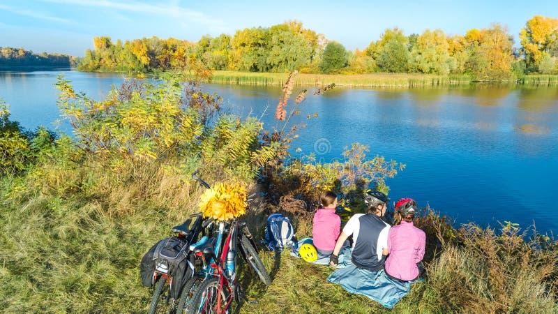 Familj på cykelhöst som utomhus cyklar, aktiv föräldrar och unge på cyklar, flyg- sikt av den lyckliga familjen med att koppla av fotografering för bildbyråer