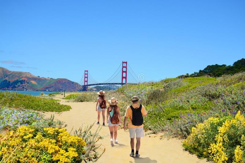 Familj på en fotvandra tur som tycker om härligt kust- landskap royaltyfri bild