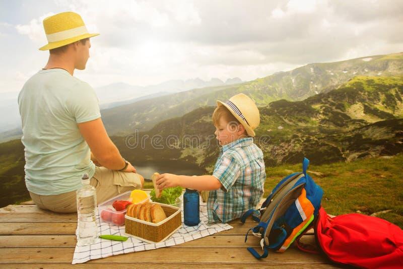 Familj på en picknick i bergen royaltyfria bilder
