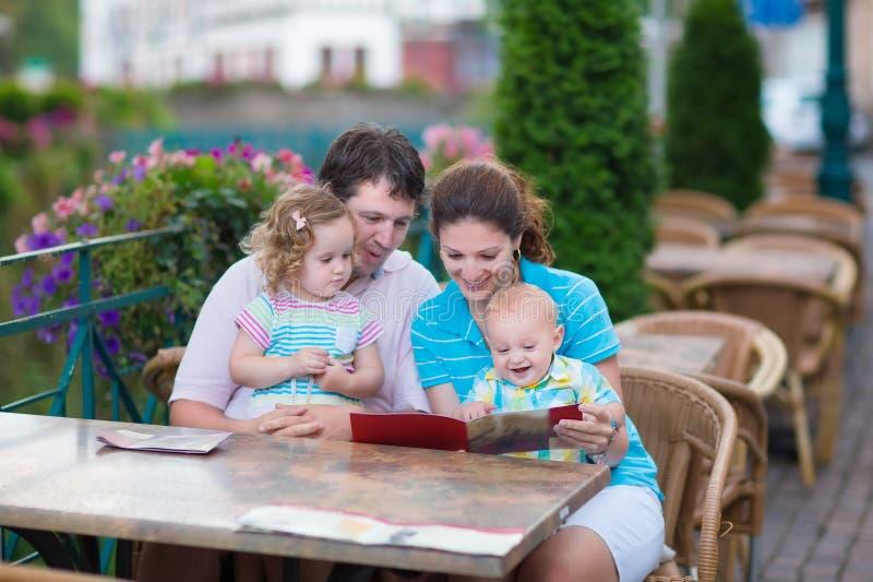 Familj på ett utvändigt kafé arkivfoton