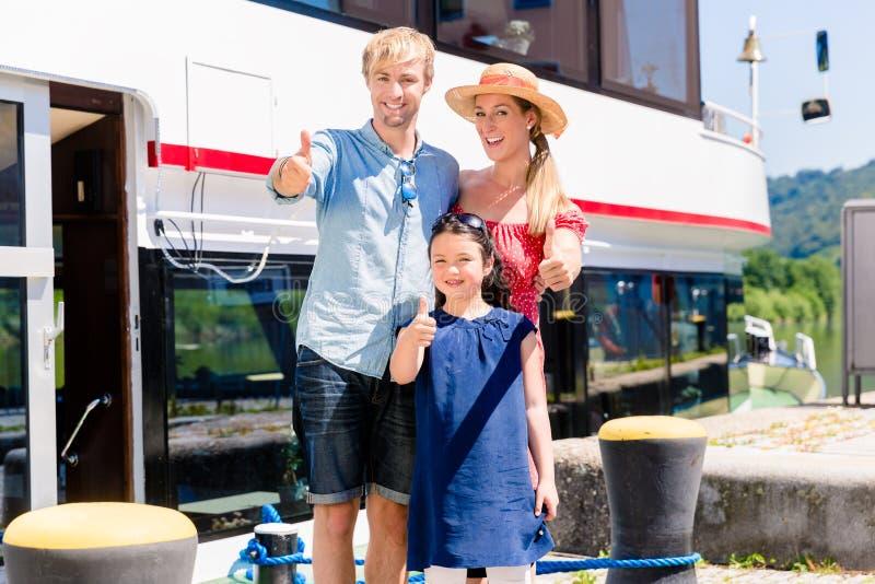 Familj på ferie framme av båtmässatummar upp arkivfoto