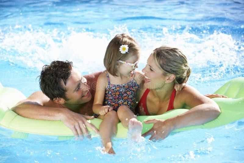 Familj på ferie i simbassäng arkivbilder