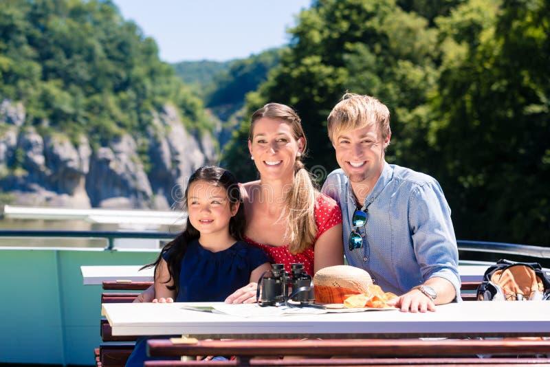 Familj på flodkryssning som ser berg från skeppdäck arkivbild