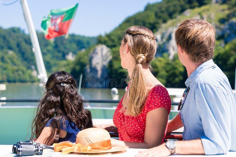 Familj på flodkryssning som ser berg från skeppdäck royaltyfri bild