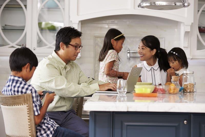 Familj på frukosten genom att använda Digital apparater royaltyfria foton