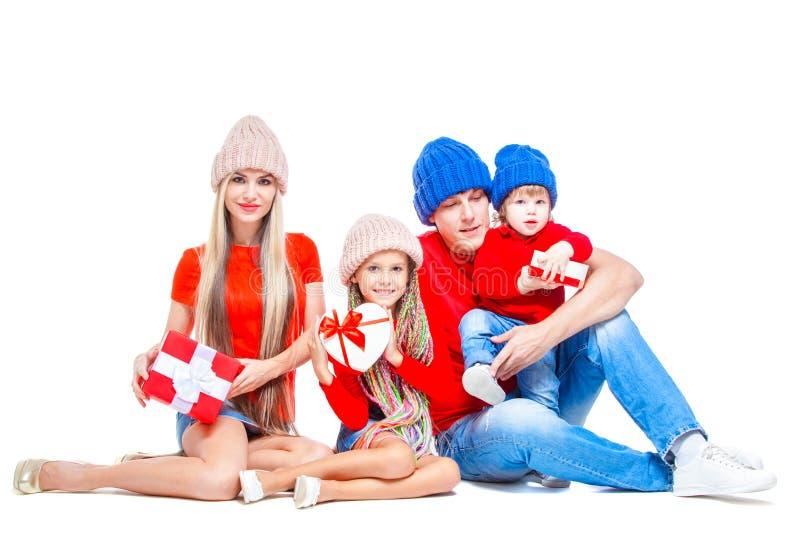 Familj på jul Gladlynt familj i hattar som ser kameran och ler, medan isolerat på vit Gåvan boxas räcker in arkivfoto