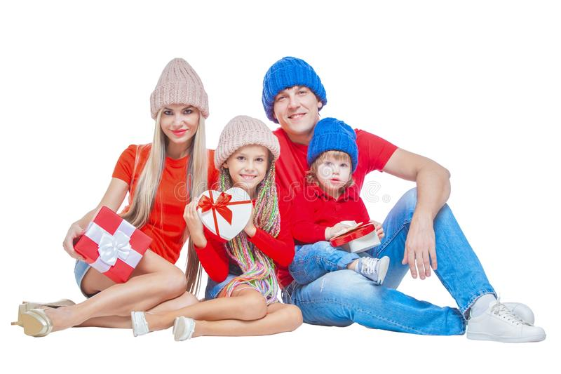 Familj på jul Gladlynt familj i hattar som ser kameran och ler, medan isolerat på vit Gåvan boxas räcker in arkivfoton