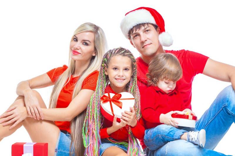 Familj på jul Gladlynt familj i jultomtenhattar som ser kameran och ler, medan isolerat på vit Stående arkivfoton