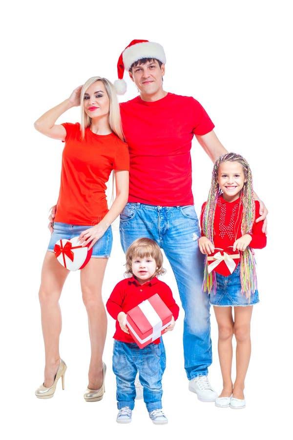 Familj på jul Gladlynt familj i jultomtenhattar som ser kameran och ler, medan isolerat på vit Stående royaltyfri foto