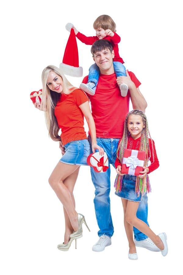 Familj på jul Gladlynt familj i jultomtenhattar som ser kameran och ler, medan isolerat på vit Stående royaltyfria bilder