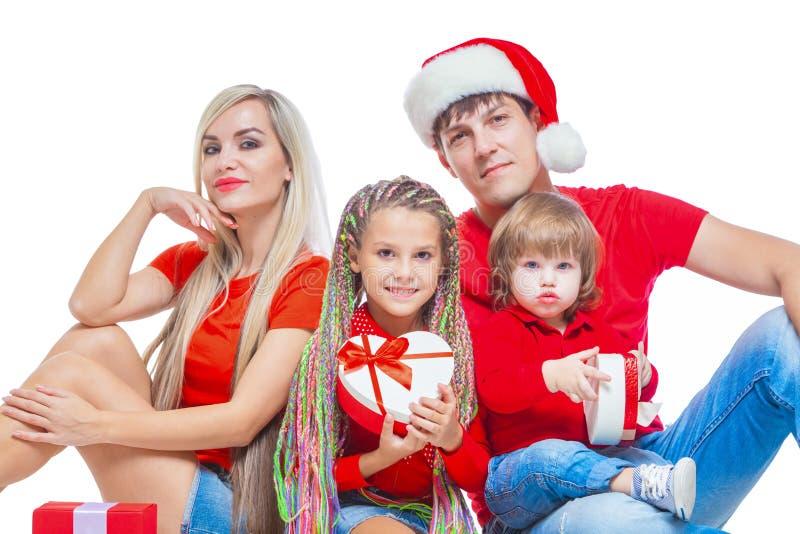 Familj på jul Gladlynt familj i jultomtenhattar som ser kameran och ler, medan isolerat på vit Stående fotografering för bildbyråer