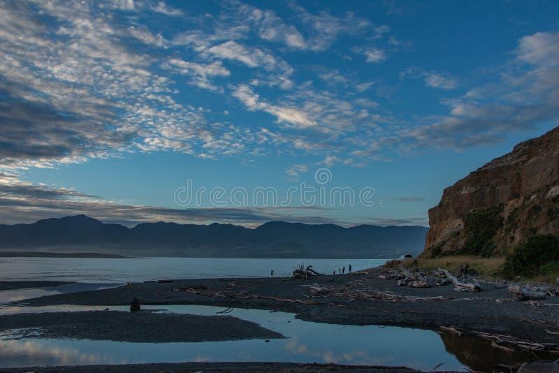 Familj på kust av sjön Onoke på skymning i södra Wairarapa fotografering för bildbyråer