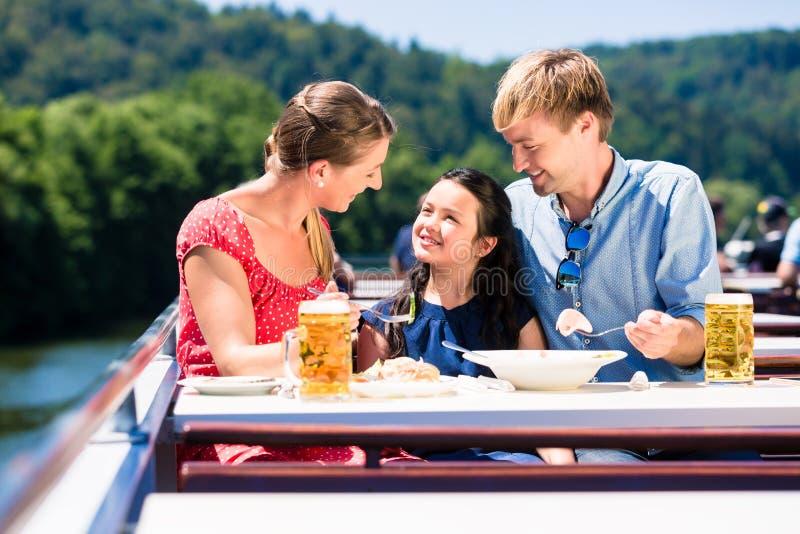 Familj på lunch på flodkryssning med ölexponeringsglas på däck royaltyfri bild