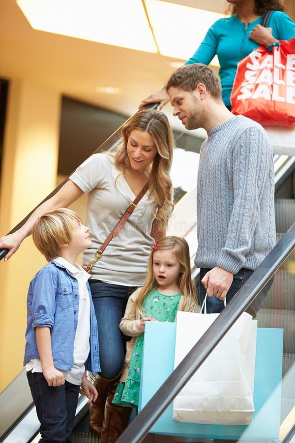 Familj på rulltrappan i shoppinggalleria tillsammans royaltyfri foto